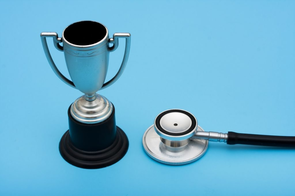 A trophy and stethoscope on a blue background, award winning healthcare services