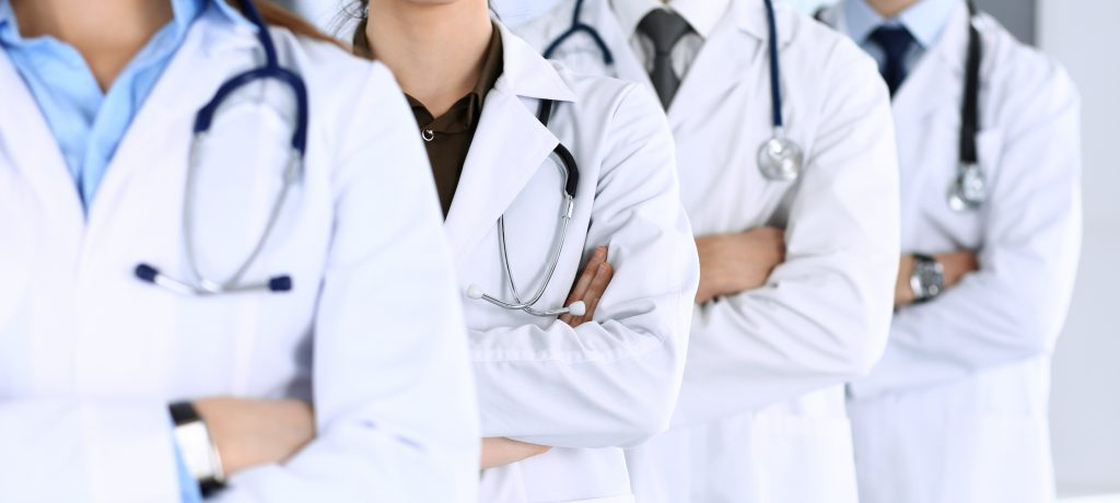 Group of modern doctors standing as a team with arms crossed in hospital office. Physicians ready to examine and help patients. Medical help, insurance in health care, best desease treatment and medicine concept.