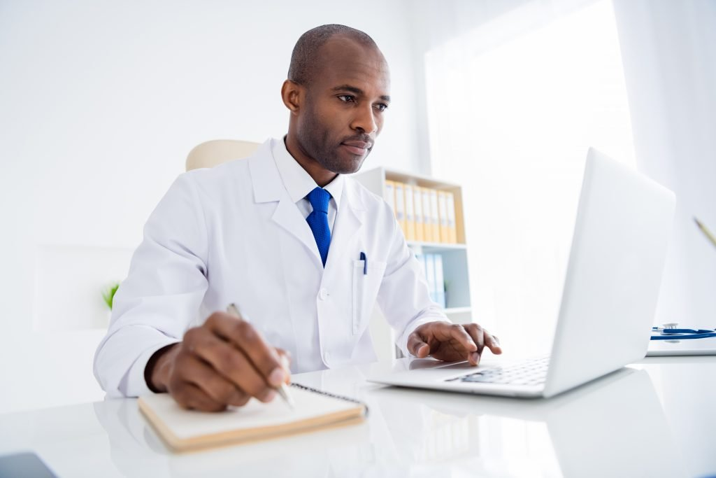 Photo of family doc dark skin guy watch notebook webinar medical reform cov viral news noting changing personal planner, wear white lab coat sitting chair table office clinic indoors